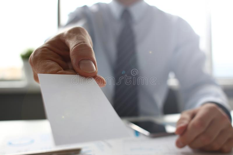 Male arm in suit give blank calling card to visitor. Closeup. White collar colleagues company name exchange job interview sale clerk id executive or ceo finance stock images