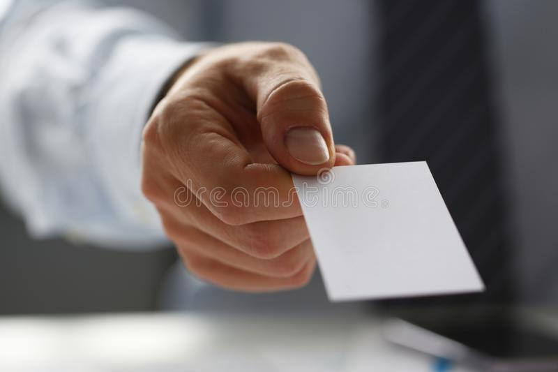 Male arm in suit give blank calling card to visitor. Closeup. White collar colleagues company name exchange job interview sale clerk id executive or ceo finance royalty free stock photo