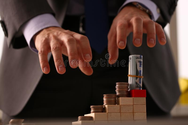 Male arm in suit reach for money closeup. Participant in financial pyramid did not have time to collect his money at moment when everything collapsed concept royalty free stock photography