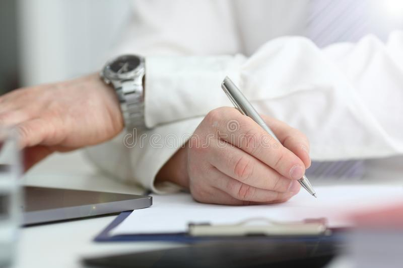 Male arm in suit and tie hold silver pen stock images
