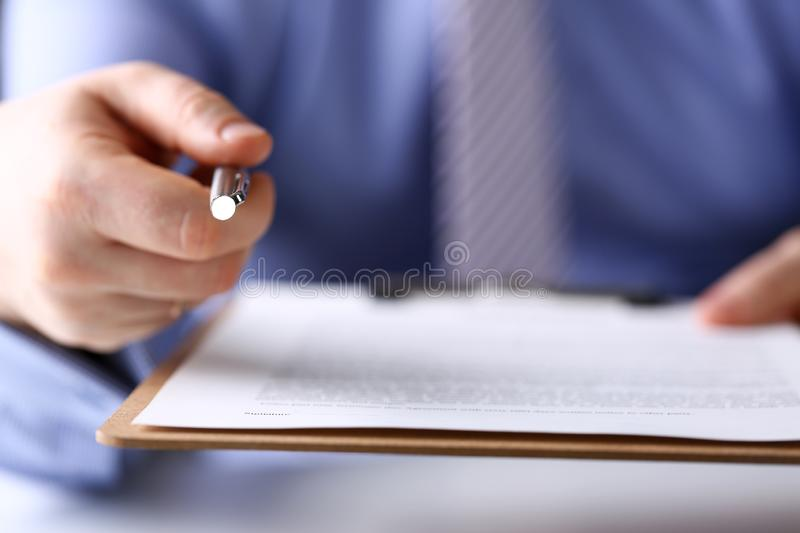 Male arm in suit and tie point in camera tip of silver pen stock images
