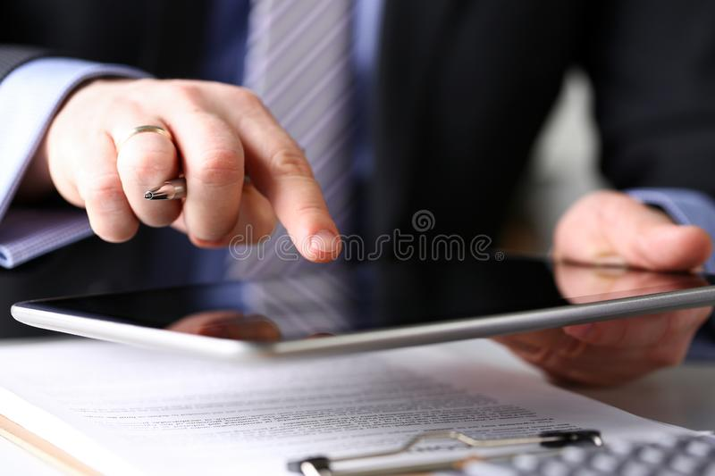 Male arm in suit and tie use silver pen and tablet pc royalty free stock photo