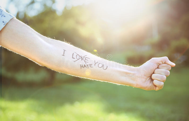 Male arm with text -I hate you- written in skin. Closeup of male arm with the text -I hate you- and word -love- crossed out in the skin over a sunny nature royalty free stock photography