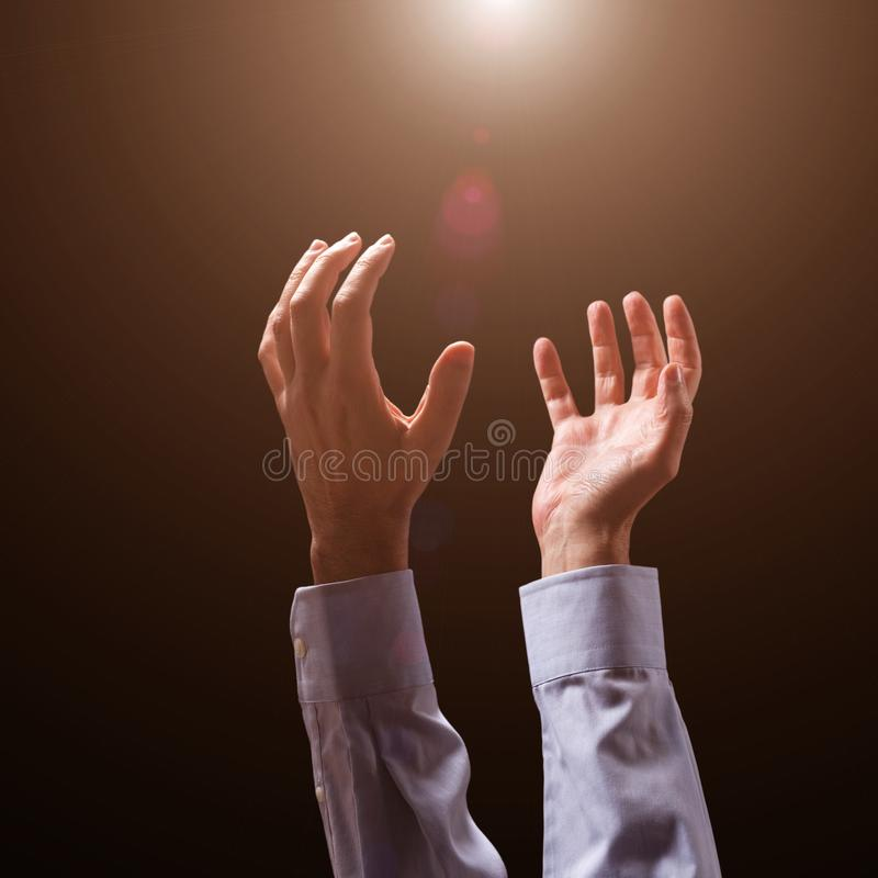 Male arms and hands raised and outstretched in the air to god. Man praying, begging, pleading imploring or supplicating. stock photography