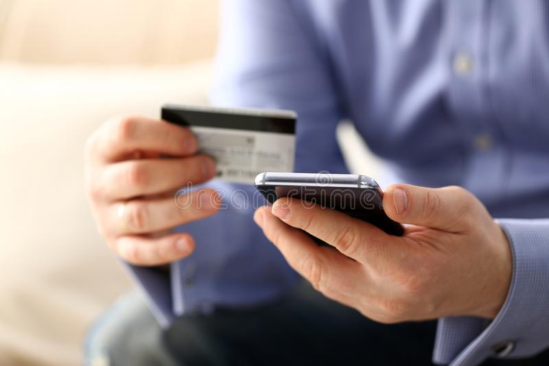 Male arms in suit hold credit card and phone make transfer stock photos