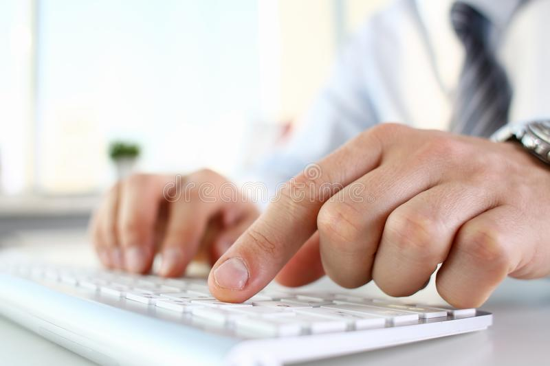Male arms in suit typing on silver keyboard royalty free stock photos