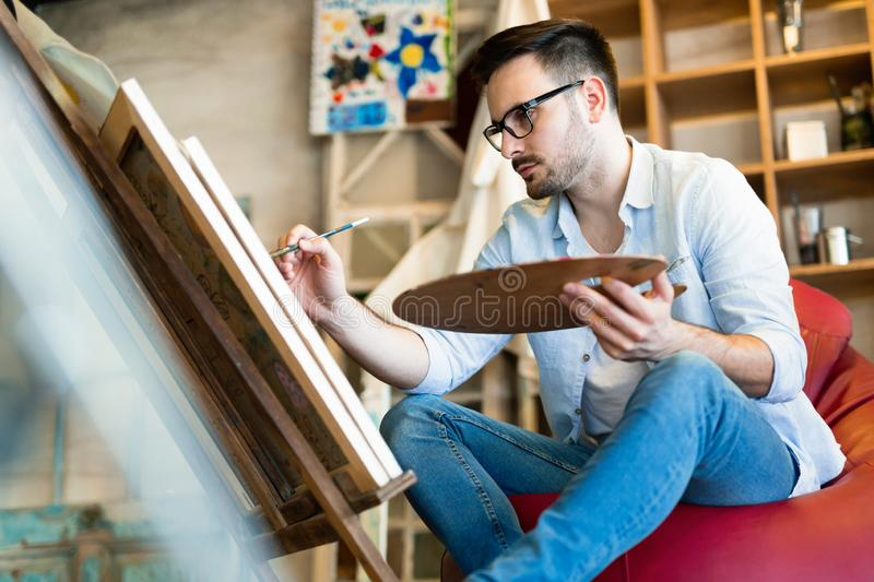 Male art school artist painting with oil on canvas stock image