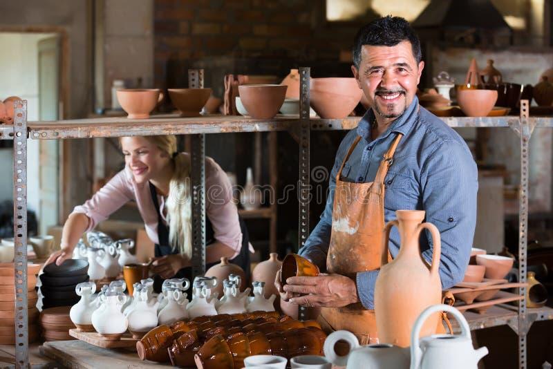 Male artisan in ceramic workshop. Cheerful smiling mature male artisan in apron holding ceramics in ceramics workshop royalty free stock image