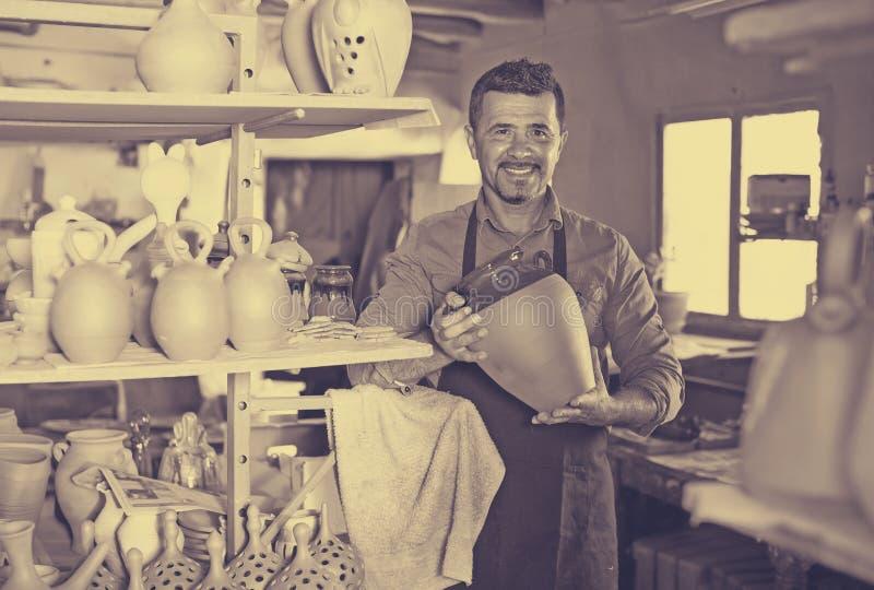 Male artisan in ceramic workshop. Cheerful smiling mature male artisan holding ceramics in hands in ceramics workshop stock image