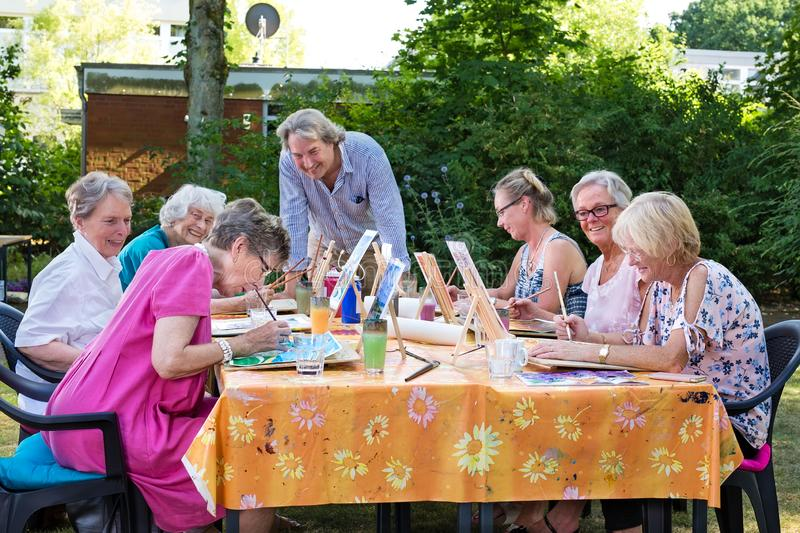 Male artist giving art lessons to the group of senior women, practicing in painting pictures sitting at one table outdoors in stock photos