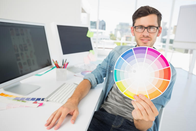 Male artist holding color wheel at desk. Portrait of a male artist holding color wheel by computer at desk royalty free stock photos