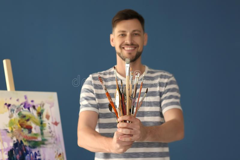Male artist holding paint tools on color background royalty free stock images