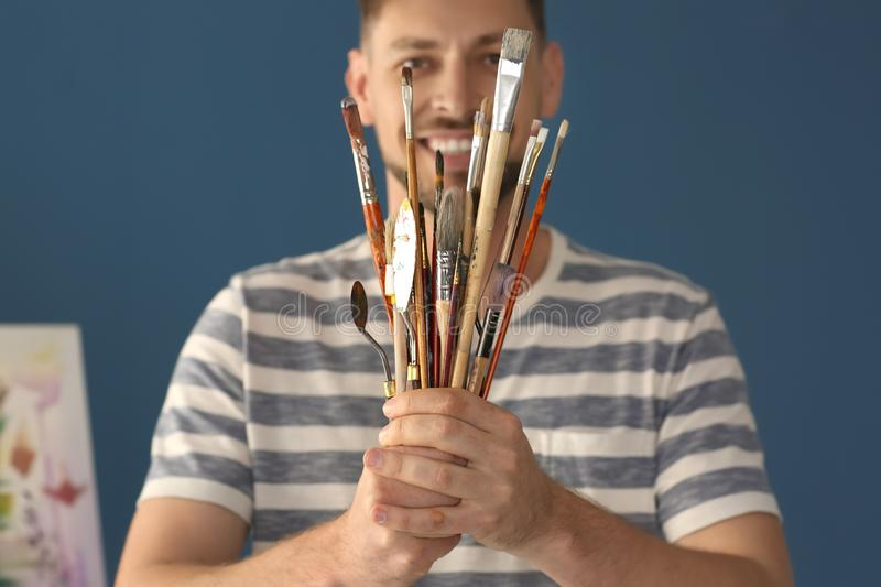 Male artist holding paint tools on color background stock images