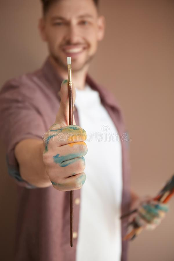 Male artist holding paintbrush on color background royalty free stock image
