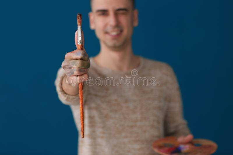 Male artist holding paintbrush on color background royalty free stock photos