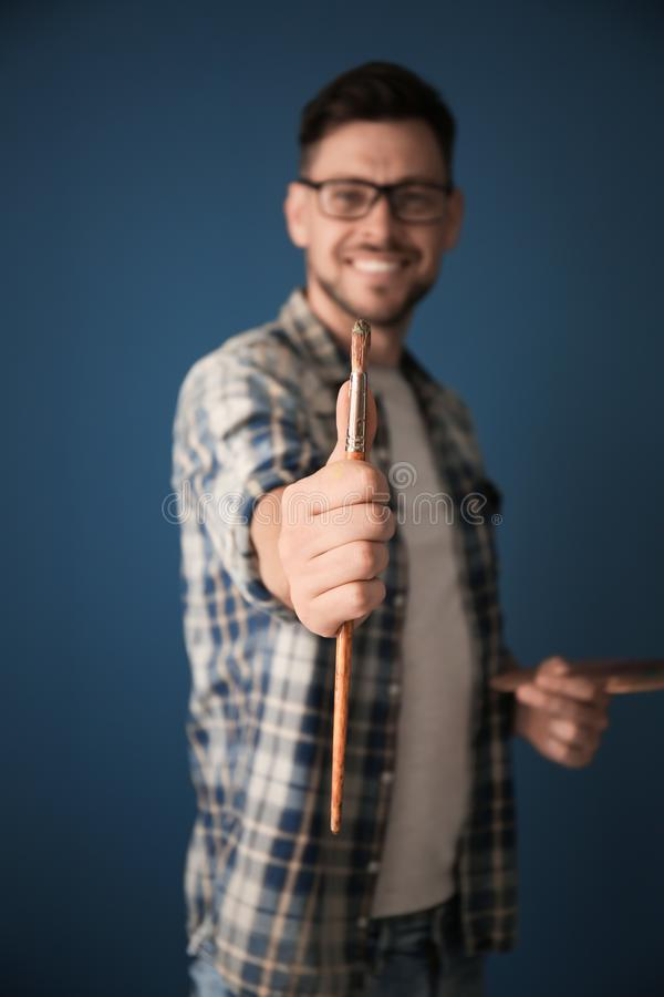 Male artist holding paintbrush on color background royalty free stock images