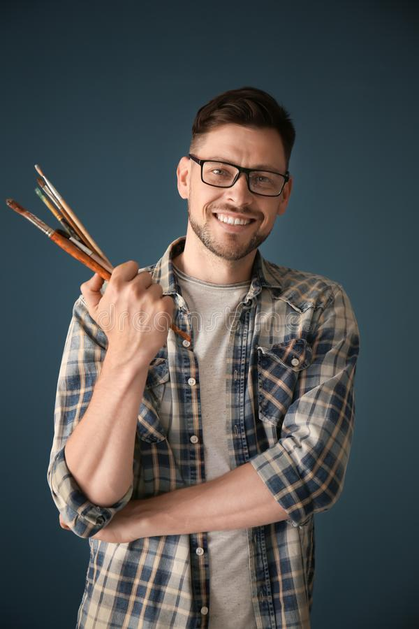 Male artist holding paintbrushes on color background royalty free stock photography