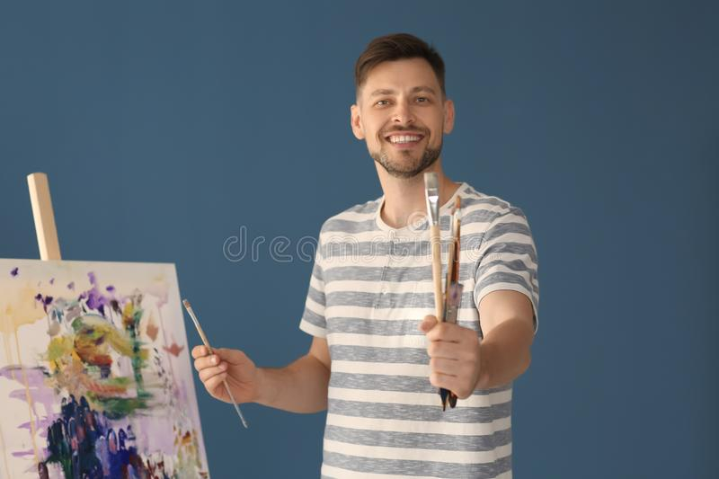 Male artist holding paintbrushes on color background royalty free stock photos