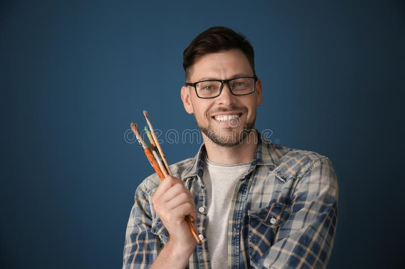 Male artist holding paintbrushes on color background stock photography