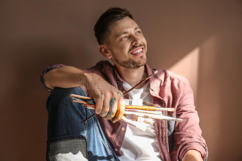 Male artist with paint tools on color background stock photography