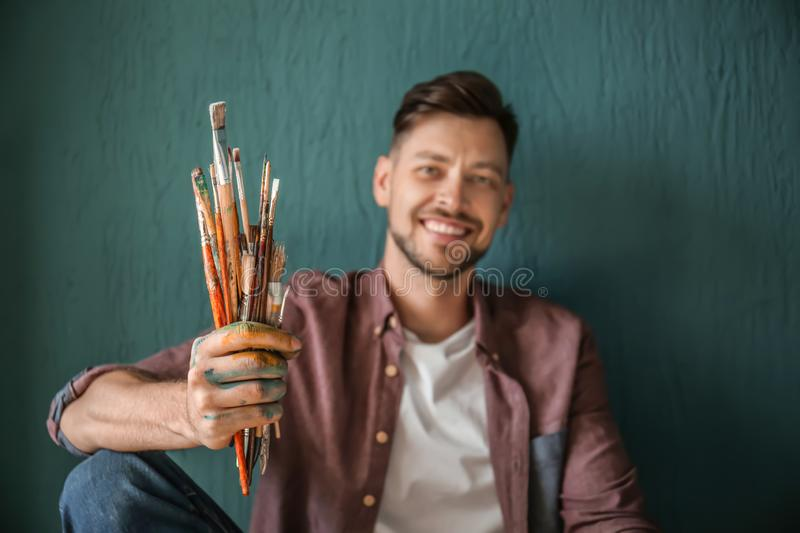 Male artist with paint tools on color background stock photos
