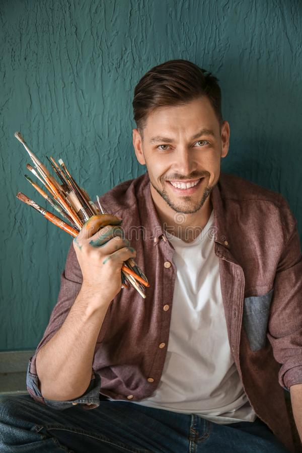 Male artist with paint tools on color background stock photo