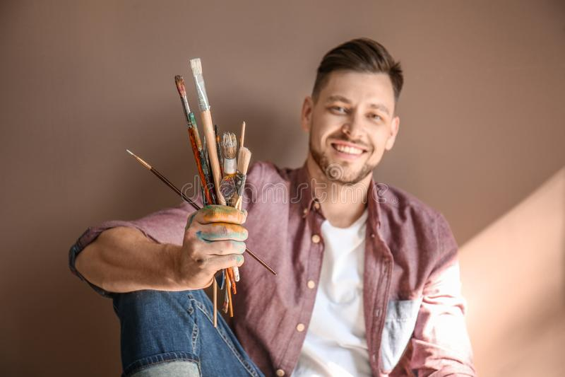 Male artist with paint tools on color background royalty free stock images