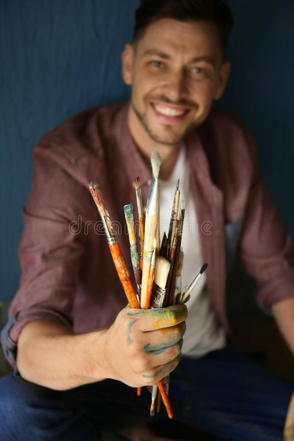 Male artist with paint tools near color wall royalty free stock photo