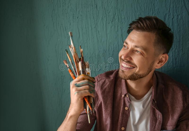 Male artist with paint tools near color wall stock image