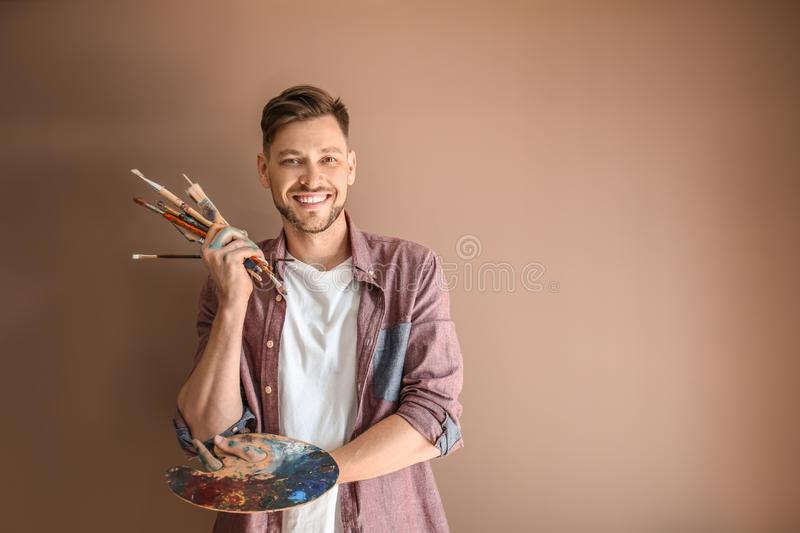 Male artist with paint tools and palette on color background royalty free stock photos