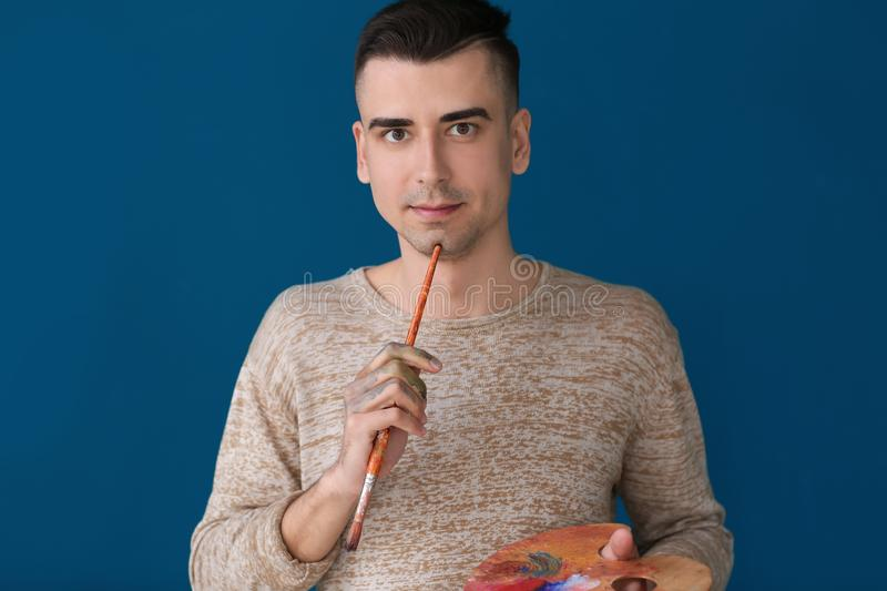 Male artist with paintbrush and palette on color background stock photo