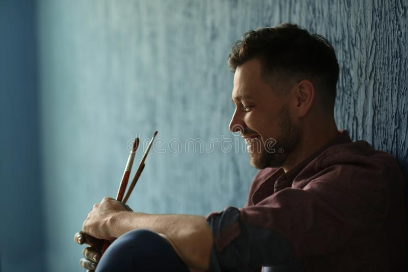Male artist with paintbrushes near color wall in workshop stock image
