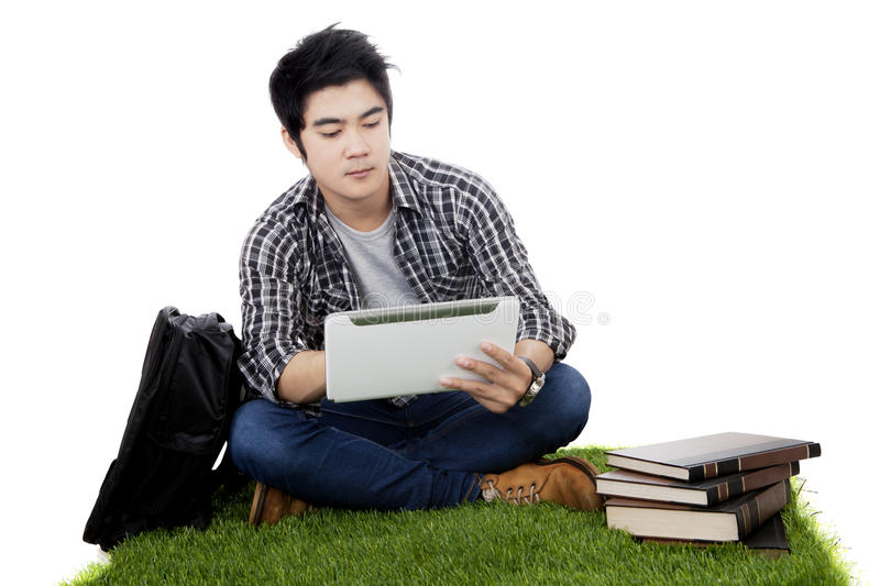 Male Asian student uses tablet on grass. Male Asian college student sitting on the grass while using a digital tablet with a bag and books around him, isolated stock image