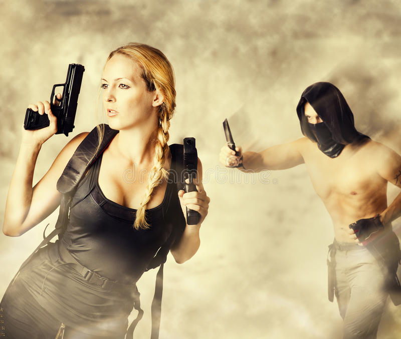 Male Assassin Attacks Woman Warrior. Male Assassin with a knife Attacks Woman Warrior holding two pistols in her hands royalty free stock photos