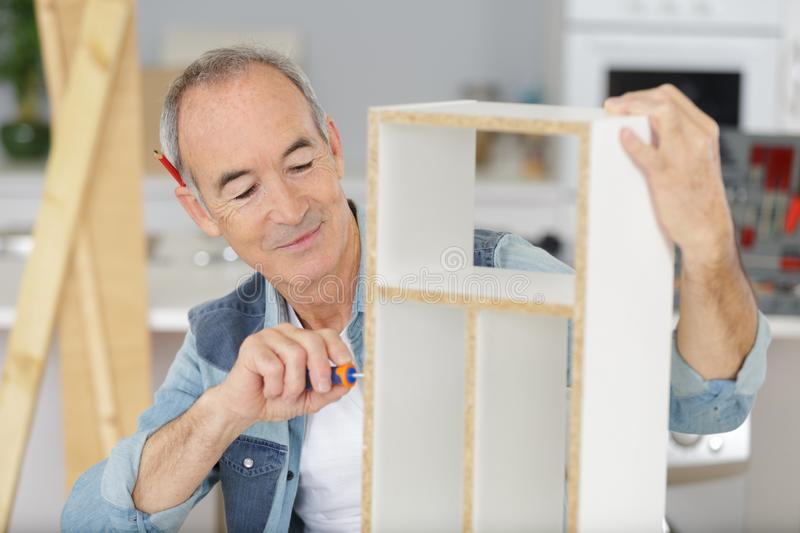 Male assembling flat pack furniture royalty free stock photography