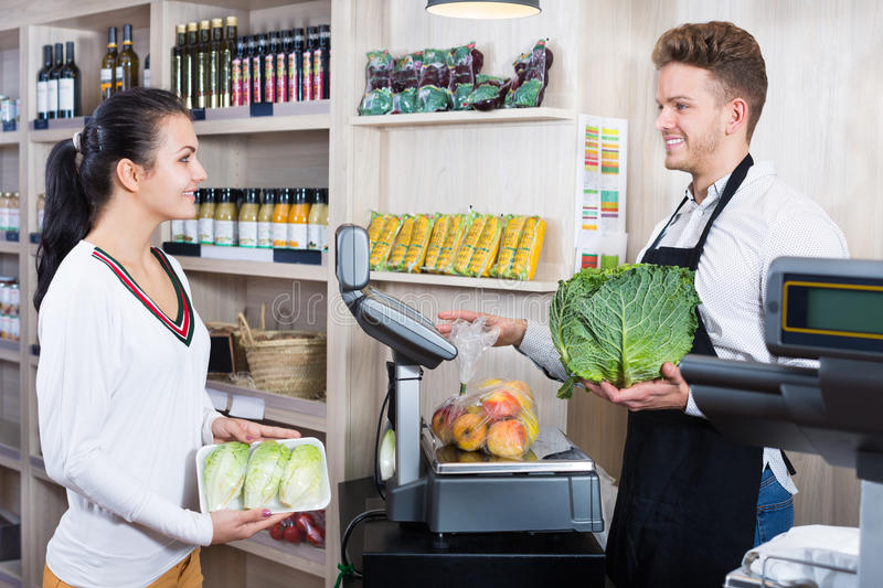 Male assistant helping customer in grocery shop royalty free stock images