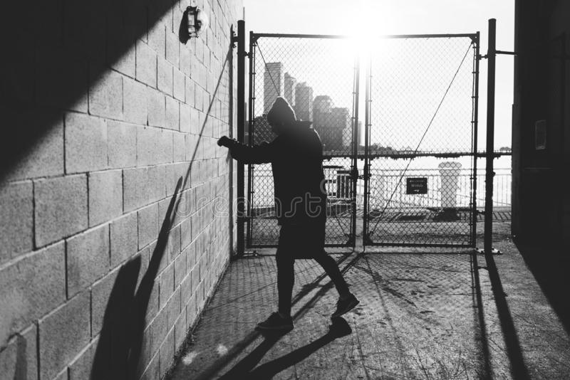 Male athlete boxing against the wall in big urban city. Sportsman training boxing in urban gateway stock photos