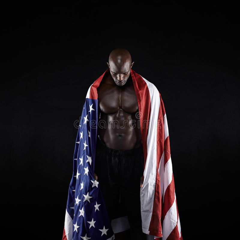 Male athlete carrying an American flag. Against black background. Studio shot of muscular sportsman with USA flag. Young man wrapped in flag stock photography