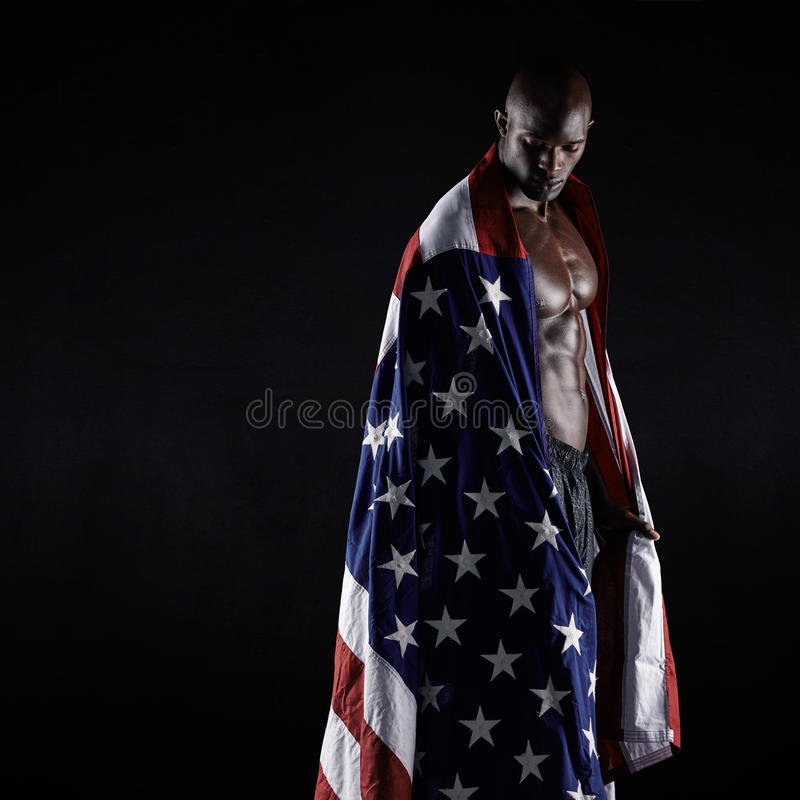 Male athlete carrying an American flag. Against black background. Studio shot of muscular sportsman with USA flag. Young man wrapped in flag stock image
