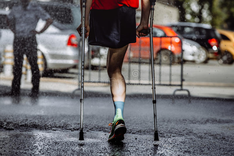 Male athlete with a disability without a leg. On crutches running marathon stock photos