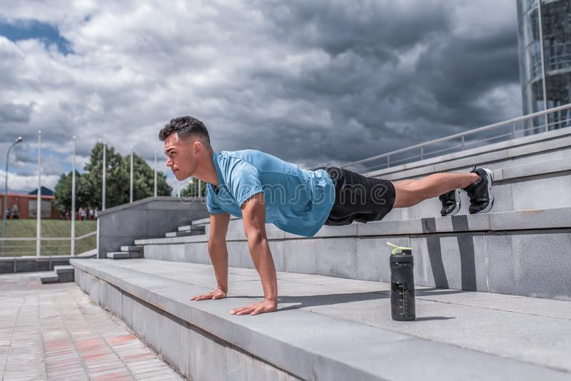 Male athlete does push-ups lying down, in spring in spring city stands at bar, an exercise on abdominal muscles. Active. Lifestyle, workout, fitness in fresh stock photo