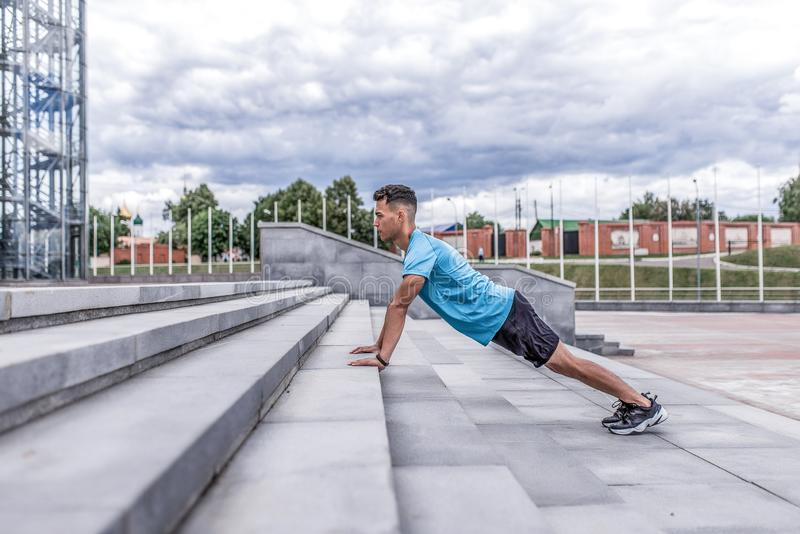 Male athlete does push-ups morning, spring summer in city, training emphasis lying. Active lifestyle, workout, fitness. In fresh air. Motivation for sports royalty free stock photos