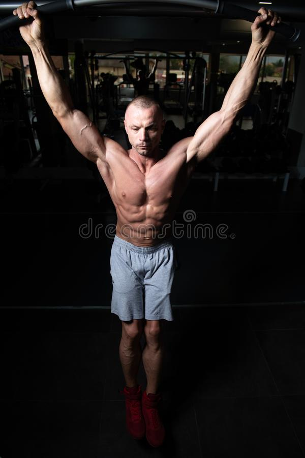 Male Athlete Doing Pull Ups. Chin-Ups In The Gym stock image