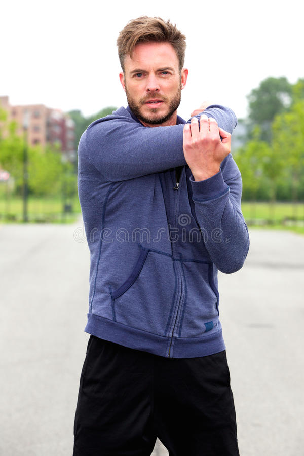 Male athlete doing stretch outside. Portrait of male athlete doing stretch outside royalty free stock photos