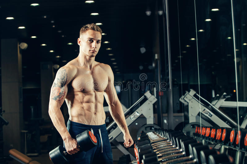 Male athlete with a dumbbell in the gym lean on. Dumbbell row royalty free stock images