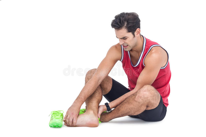 Male athlete with foot pain on white background. Male athlete with foot pain on isolated white background royalty free stock photography