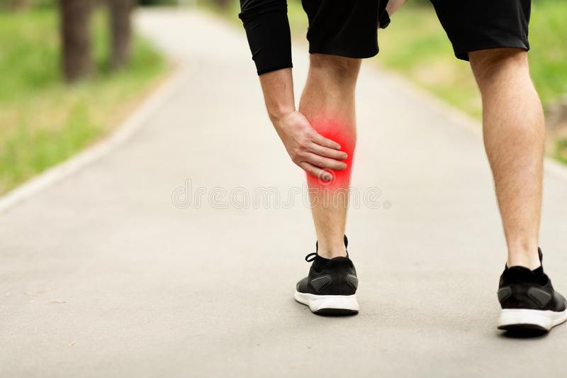 Man massaging painful calf muscle with red sore spot outdoors. Male athlete with injured calf, massaging painful leg muscle with red sore spot suffering from royalty free stock photography