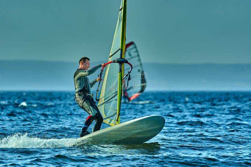 A male athlete is interested in windsurfing. He moves on a Sailboard on a large lake stock images
