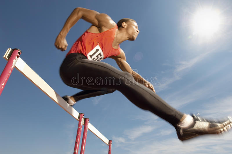 Male Athlete Jumping Over A Hurdles. Low angle view of determined male athlete jumping over a hurdles stock image