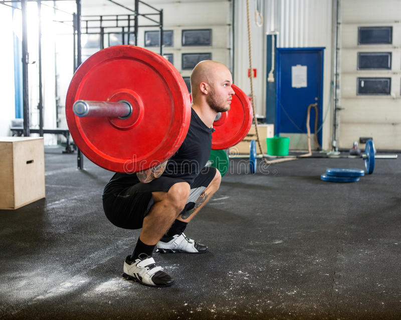 Male Athlete Lifting Barbell At Gym. Full length young male athlete lifting barbell while trainer looking at him in gym royalty free stock images
